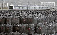JR常磐線の富岡駅と竜田駅間の運行が再開され、富岡駅を出る上り電車。手前は除染で出た廃棄物を入れた袋の仮置き場=福島県富岡町で2017年10月21日午前8時32分、西本勝撮影
