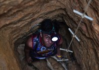 Christopher Jude Edria is seen digging for gold ore in a 6-meter-deep hole in Camarines Norte Province in the Philippines, on July 29, 2017. (Mainichi)