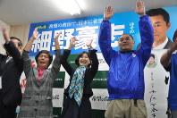 細野豪志氏が党務で東京に行き不在の中、支援者と万歳する妻節さん(中央)=三島市の事務所で22日午後8時9分