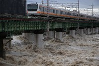 Suffering delays due to Typhoon Lan, a JR Chuo Line train passes over the swollen Tama River, in the Tokyo suburban city of Hino, on the morning of Oct. 23, 2017. (Mainichi)