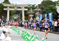 1区、世界文化遺産に登録された宗像大社辺津宮の前を駆け抜ける選手たち=福岡県宗像市で2017年10月22日、徳野仁子撮影