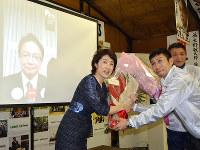 大野敬太郎氏が映るテレビ電話の前で花束を受け取る妻いと子さん(左)=香川県観音寺市の事務所で2017年10月22日午後8時、山中尚登撮影