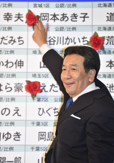 Yukio Edano, leader of the Constitutional Democratic Party of Japan (CDP), places a flower next to the name of a candidate in the party assured of victory in the Oct. 22 House of Representatives election, on the evening of Oct. 22, 2017. (Mainichi)