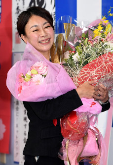 Shiori Yamao smiles while holding flowers in the city of Nagakute, Aichi Prefecture, after her expected victory was projected, on Oct. 23, 2017. (Mainichi)