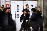 People heading to Toshiba's extraordinary shareholders meeting go through a security check at the meeting venue in Chiba's Mihama Ward on Oct. 24, 2017. (Mainichi)