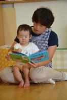 0歳児クラスの子に絵本の読み聞かせをする保育士=東京都内の認可保育所で、堀井恵里子撮影