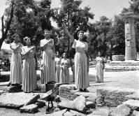 採火式。凹面鏡に集めた太陽の光から採火した聖火をかかげ、ゼウスの神へ祈る主みこのカッツェリ夫人(手前右端)=ギリシャ・オリンピアのヘラ神殿跡で 1964年8月20日、橋本紀一特派員撮影 (採火式本番は非公開。前日に公開されたリハーサルで)