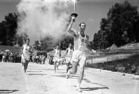 聖火のトーチを掲げ、随走者を従えて走る聖火リレー第1走者のマルセロス選手=ギリシャ・オリンピアで 1964年8月20日、橋本紀一特派員撮影(前日のリハーサルで)