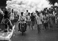聖火はニューデリーに到着。沿道から飛び出し聖火ランナーと一緒に走る子供たち=インドで 1964年8月28日、橋本紀一特派員撮影