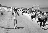聖火が沖縄に到着し、那覇空港での式典の後、市内に向け走る第1走者の宮城勇さんと随走者。それを追いかける地元の少年たち=沖縄・那覇市内で 1964年9月7日、橋本紀一撮影