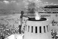 奥武山陸上競技場の聖火台に点火する宮城康次さん。競技場は3万5000人の市民でうまった=沖縄・那覇市で 1964年9月7日、鈴木久俊撮影