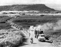 戦跡、麻文仁の丘を背にひた走る聖火ランナーの金城安秀さんと随走者=沖縄・糸満市で 1964年9月8日、橋本紀一撮影