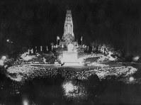 沖縄から空路運ばれた聖火は、宮崎市の平和台公園・平和の塔に設けられた聖火台に点火された。宵闇に炎が浮かぶと集まった2万人の観衆から歓声があがった=宮崎市で 1964年9月9日撮影