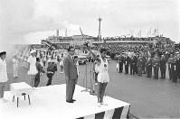 千歳空港で聖火を掲げる第1走者の笹野弘康さん。左は町村金五・北海道知事=北海道千歳市で1964年9月9日撮影