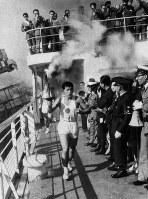 青森に向かう青函連絡船「津軽丸」のデッキで、聖火を掲げて走る北海道最終走者の小沼さん=1964年9月17日撮影