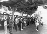 東北本線・青森駅のホームを走る聖火ランナー=青森市で 1964年9月17日撮影