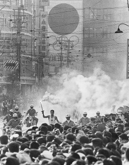 暮色迫る北九州市のメインストリートを走りぬける聖火。走者は江頭正さん=福岡県北九州市小倉魚町で 1964年9月17日午後5時15分撮影