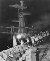 台風の影響で兵庫から大阪までの走者による聖火リレーが中止になり、代わりに「聖火の夕べ」が開かれ、走者たちが大阪プールのプールサイドをトーチを掲げて走った=大阪市北区で 1964年9月25日、谷田貝高幸撮影