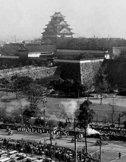 大阪府庁を出発し和歌山市を目指す聖火、後方は大阪城=大阪市で 1964年9月26日、本社ヘリから坂口喜三撮影