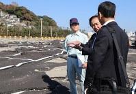 風雨による甚大な被害を受け、アスファルトが波打った状態の駐車場を視察する黒岩知事=藤沢市江の島で