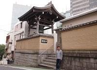 円通寺坂を上ったところ、赤坂の台地の上にある円通寺の前にたたずむ一之輔さん。奥にTBSが見える=東京都港区で