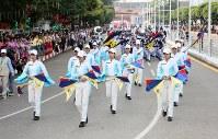 「第22回世界のお巡りさんコンサートinミャンマー」フラッグを回してパレードするミャンマー警察の女性警察官部隊=ヤンゴン市内で2017年10月28日午前、松田嘉徳撮影