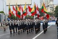 「第22回世界のお巡りさんコンサートinミャンマー」参加国の国旗を掲げてパレードするミャンマー警察の女性警察官部隊=ヤンゴン市内で2017年10月28日午前、松田嘉徳撮影