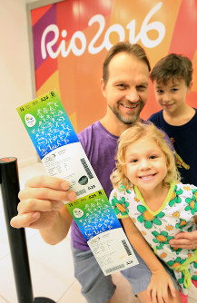 A father and his children express joy after acquiring tickets for the 2016 Olympics in Rio, on July 3, 2016. (Mainichi)