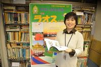 ラオスの教科書を手に、今年の教科書展の看板前で取材に応じる山川智子准教授。後ろに世界各国の教科書などが並ぶ=越谷市の文教大で
