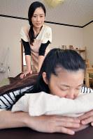 「お体の具合はどうですか」。ベッドに横になった頴原千絵さん(手前)に語りかけながら施術する辻浦しのぶさん=和歌山県高野町で、花澤茂人撮影
