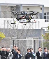昨年4月に千葉市の幕張新都心で行われた実証実験で、デモンストレーション飛行する宅配用ドローン=千葉市美浜区で、宮間俊樹撮影