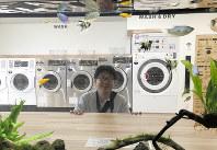 水槽ごしに笑顔を見せる=東京都江戸川区の「AQUARIUM LAUNDRY」で