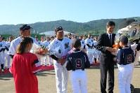 井口監督(中央)らに地元の小学生から歓迎の花束が贈られた=鴨川市営球場で