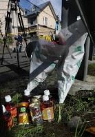 現場のアパートそばに供えられた花束と9本の飲み物=神奈川県座間市で、小出洋平撮影
