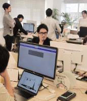 若手社員に囲まれて仕事するアトラエの新居佳英CEO(中央)=東京都港区のアトラエ本社で、鳴海崇撮影