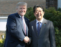 Prime Minister Shinzo Abe, right, shakes hands with U.S. President Donald Trump at Kasumigaseki Country Club in Kawagoe, Saitama Prefecture, shortly after midday on Nov. 5, 2017. (Pool photo)