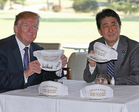 Prime Minister Shinzo Abe, right, and U.S. President Donald Trump hold up signed caps bearing the message,