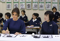 U.S. first lady Melania Trump uses a brush to write a character for the word