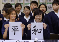 U.S. first lady Melania Trump, left, and Japanese Prime Minister Shinzo Abe's wife Akie show off calligraphy they wrote as they attend a calligraphy class of the 4th grader at Kyobashi Tsukiji Elementary School in Tokyo, on Nov. 6, 2017. The calligraphy reads: