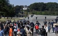トランプ米大統領の到着前、皇居周辺の警戒にあたる警察官と皇居前広場の外に出る観光客ら=東京都千代田区で2017年11月6日午前10時27分、竹内紀臣撮影