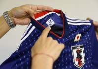 2018年W杯ロシア大会を前に発表されたサッカー日本代表の新しいユニホーム。首元の内側のロゴは過去のユニフォームのデザインが組み合わされている=東京都文京区で2017年11月6日、佐々木順一撮影