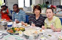 ボランティアや相談者と一緒に食卓を囲み、笑顔を見せる松浦・デ・ビスカルド篤子さん(右から2人目)=大阪市中央区玉造2のシナピスで、金志尚撮影