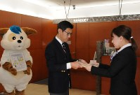 アンケート用紙をホテル側に手渡し、協力を呼びかける旭川中央署の佐藤厚・刑事生活安全官(左)=旭川市で