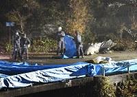 墜落したヘリコプターの機体を調べる捜査員ら=群馬県上野村で2017年11月8日午後6時50分、藤井達也撮影