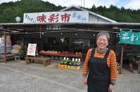 直売所の「きんかい味彩市」の前で笑顔を見せる佐木さん