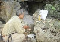 ガマで収容した遺骨にお茶をささげ、手を合わせる具志堅隆松さん=沖縄県糸満市で9月