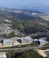 The construction site of a Kake Educational Institution veterinary school, foreground, is seen from a Mainichi Shimbun helicopter in Imabari, Ehime Prefecture, on Nov. 10, 2017. The Setouchi Shimanami Kaido Expressway is seen in the background. (Mainichi)