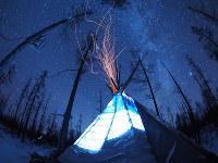 冬の星空とオルツ(モンゴル語で円錐型の移動式住居)。薪を燃やして室内を暖めているため、上空に火の粉が舞う=2016年12月、写真家の清水哲朗さん撮影