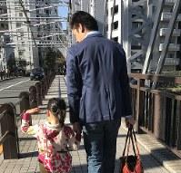 保育所まで仲良く手をつないで歩く親子=東京都内で、坂根真理撮影