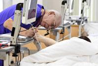 患者を診察する武蔵台病院の西蔵ツワン院長=9月19日、竹内紀臣撮影
